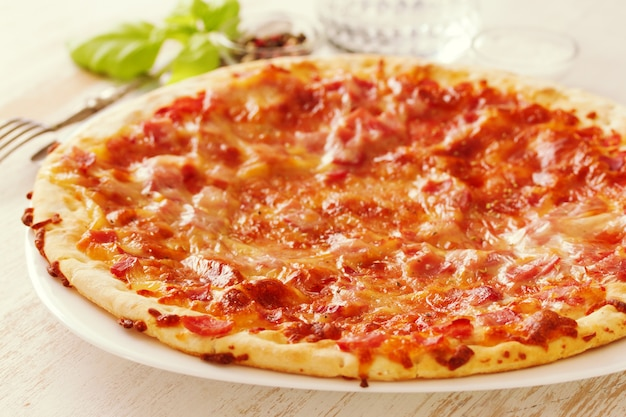 Pizza su superficie di legno bianca