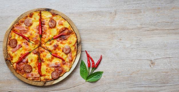 Pizza sul vassoio di legno e basilico dei peperoncini rossi