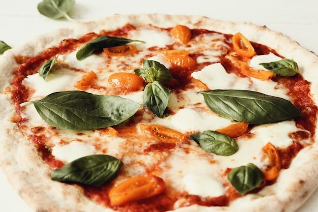 Pizza sulla tavola di legno bianca