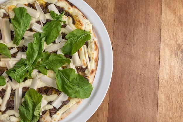Pizza sulla tavola di legno marrone