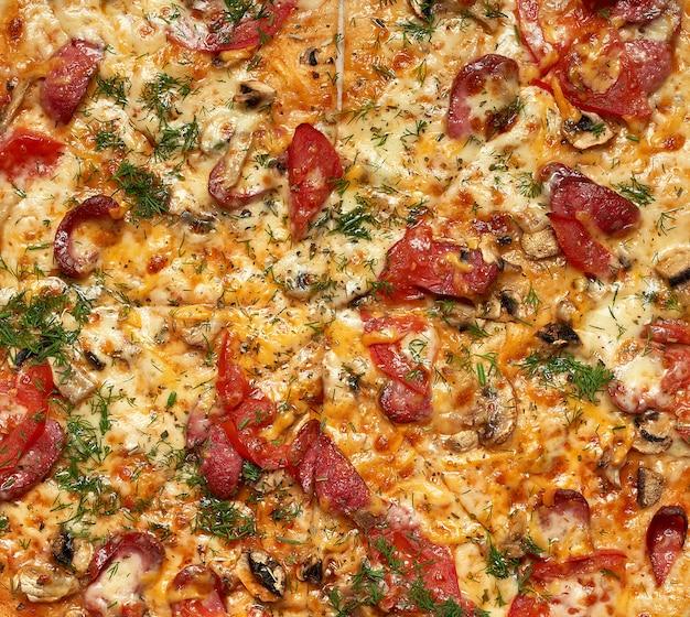 Pizza tonda al forno con salsicce affumicate, funghi, pomodori, formaggio e aneto