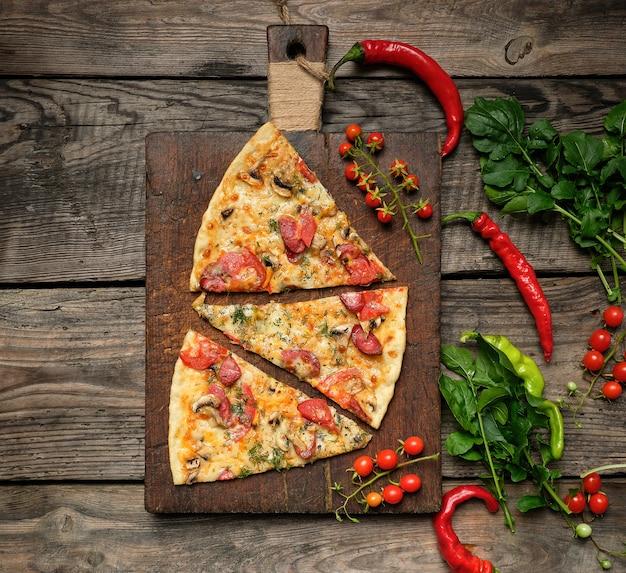 Pizza tonda al forno con salsicce affumicate, funghi, pomodori, formaggio