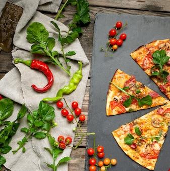 Pizza tonda al forno con salsiccia affumicata, funghi, pomodori, formaggio e foglie di rucola,
