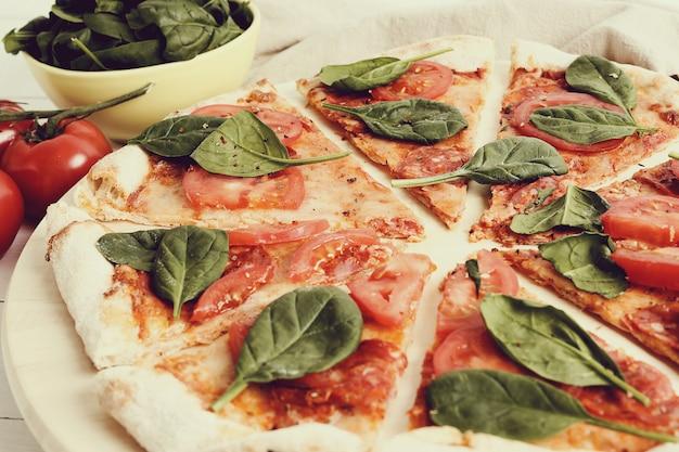 Pizza tradizionale con fette di pomodoro e foglie di basilico