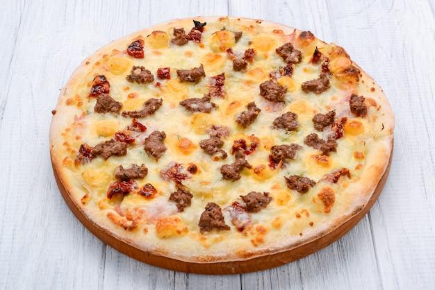 Pizza tritata della cipolla rossa del pomodoro della carne su una tonalità di superficie di legno