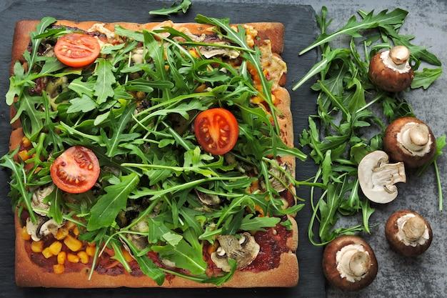 Pizza vegana con funghi e rucola fresca. pizza quadrata con verdure, funghi e rucola.