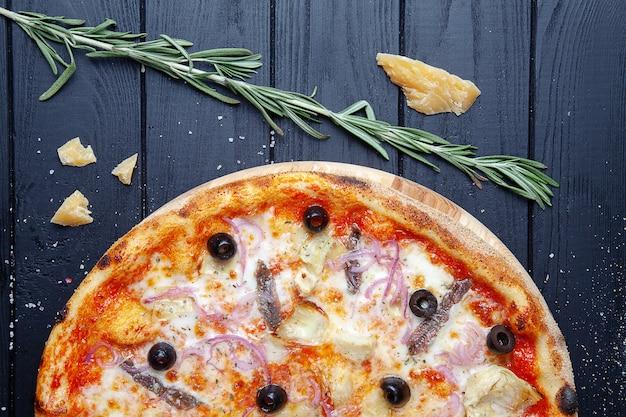 Pizza vista dall'alto con acciughe, olive, formaggio e cipolle su fondo di legno scuro con ingridients. pizza italiana con frutti di mare sfondo di cibo. gustosa pizza fatta in casa con cucina italiana. fast food