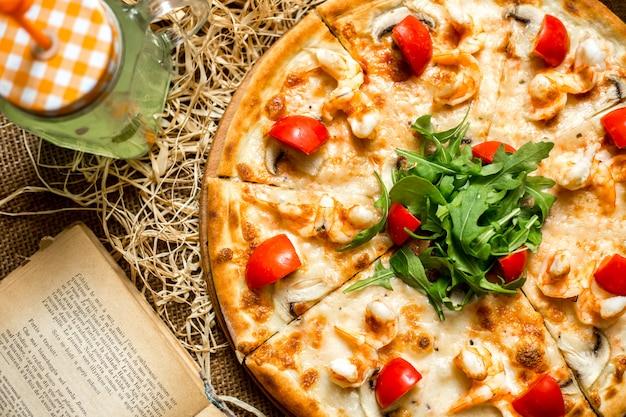 Pizza vista dall'alto con gamberi e funghi pomodori e rucola e con una bibita analcolica