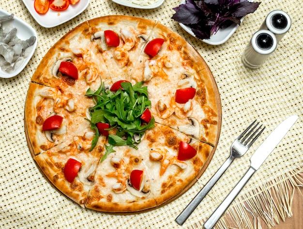 Pizza vista dall'alto con gamberi e funghi pomodori e rucola
