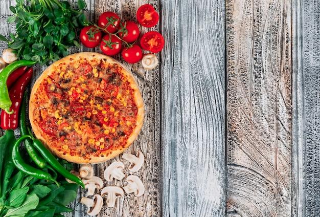 Pizza vista dall'alto con peperoni, funghi, pomodori e verde su sfondo di stucco chiaro. verticale