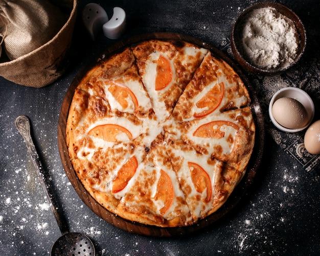 Pizza vista dall'alto con pomodori rossi e formaggio sulla scrivania grigia
