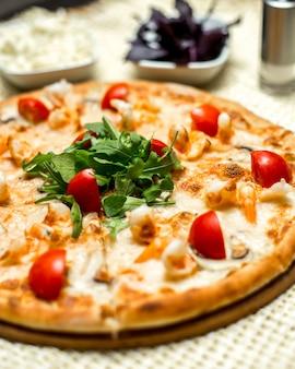 Pizza vista frontale con gamberi pomodori e rucola