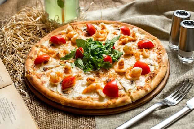 Pizza vista laterale con gamberi e funghi pomodori e rucola e con una bibita analcolica