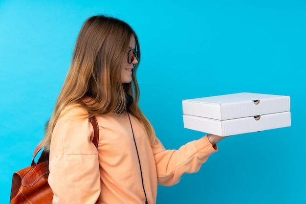 Pizze della tenuta della ragazza dell'adolescente sopra la parete blu isolata