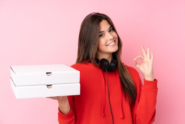 Pizze della tenuta della ragazza dell'adolescente sopra la parete rosa