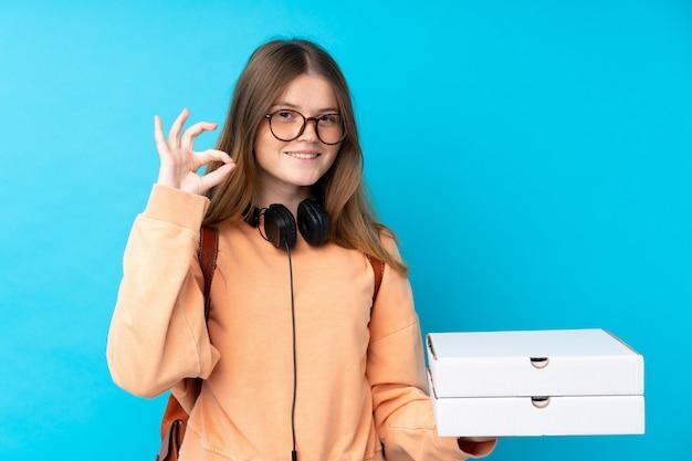 Pizze ucraine della tenuta della ragazza dell'adolescente sopra la parete blu isolata che mostra segno giusto con le dita