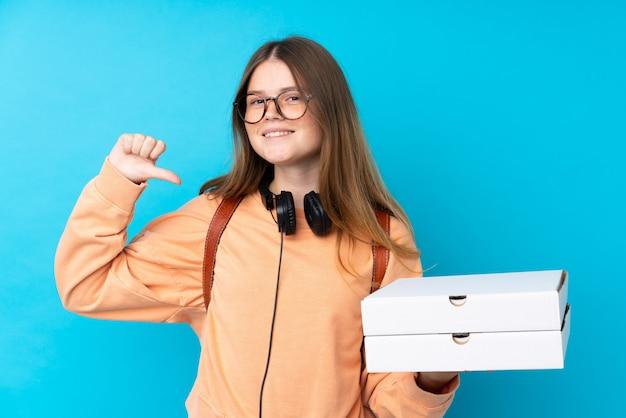 Pizze ucraine della tenuta della ragazza dell'adolescente sopra la parete blu isolata fiera e soddisfatta