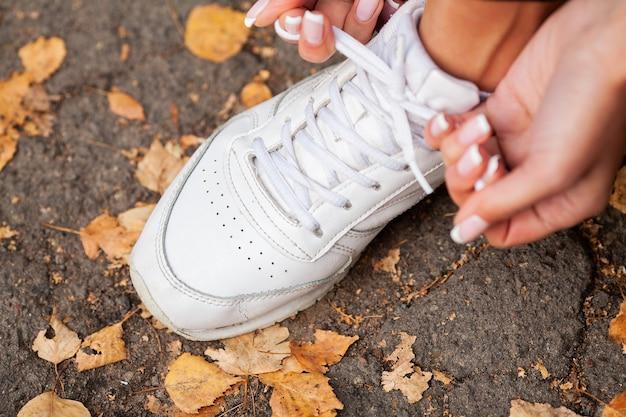 Pizzo scarpa stringente runner donna. piedi della donna del corridore che corrono sul primo piano della strada sulla scarpa