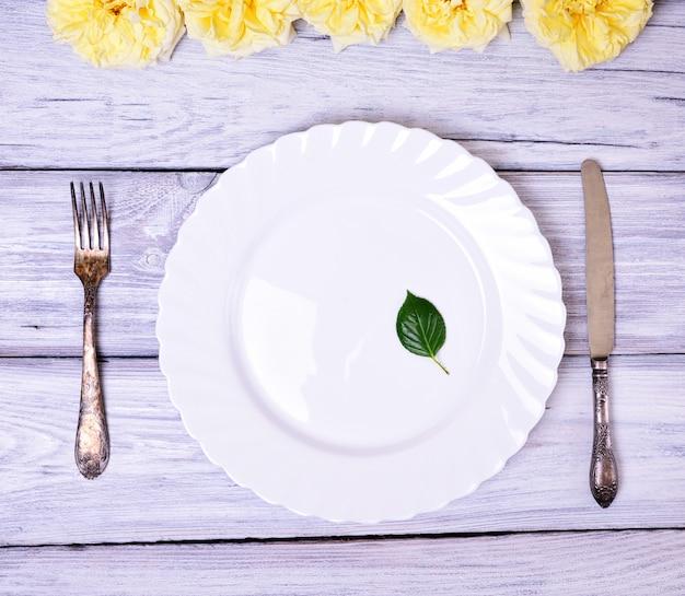 Placca bianca vuota e forchetta e coltello in metallo