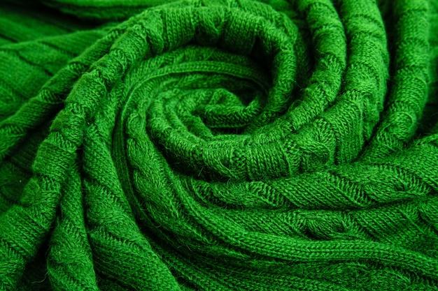 Plaid arrotolato verde, treccia lavorata a maglia