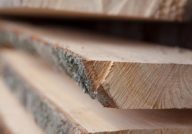 Plance di legno piegate in una segheria. tavole accatastate come texture.