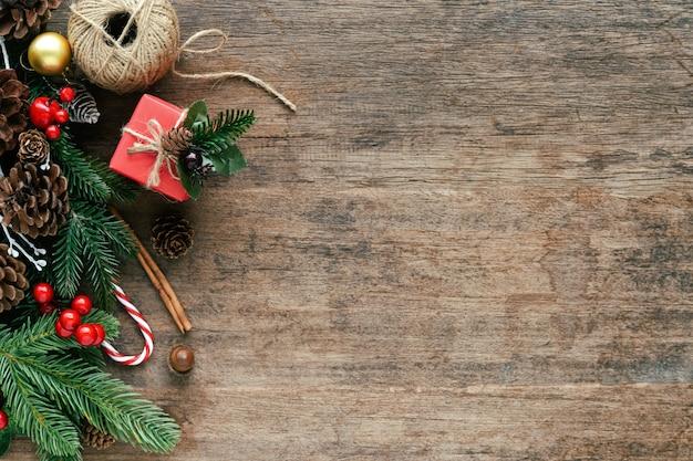 Plancia di legno con le foglie di pino, le pigne, le palle dell'agrifoglio, il contenitore di regalo e il bastoncino di zucchero nel concetto di natale.