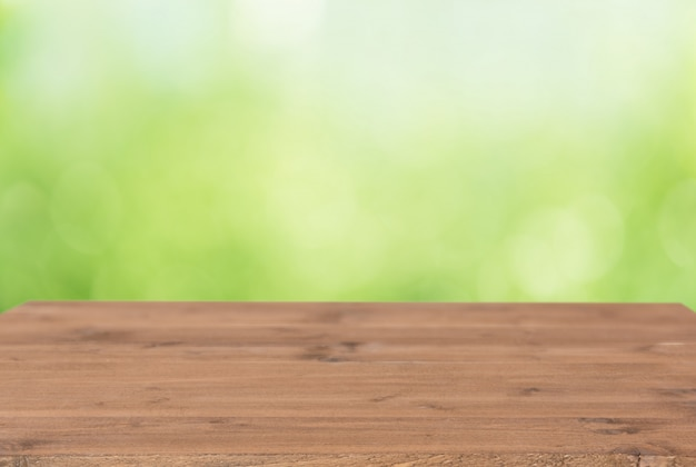 Plancia di legno di brown con il fondo verde variopinto della sfuocatura