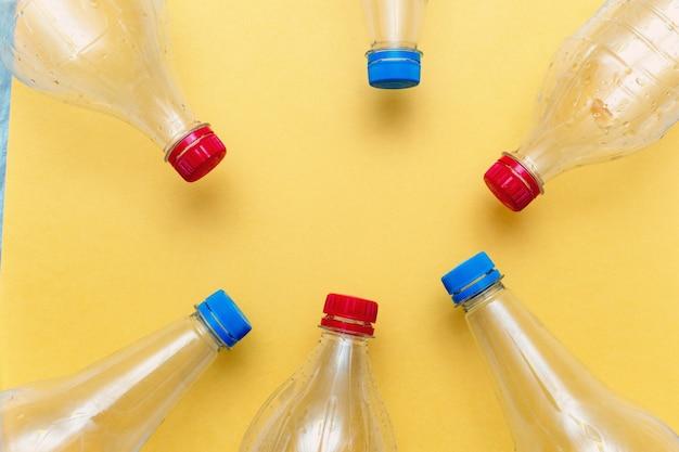 Plastica usata, bottiglie vuote su sfondo giallo con spazio di copia