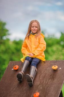 Playng felice della bambina sul campo da giuoco all'aperto