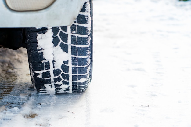 Pneumatici auto su strada invernale coperto di neve. veicolo in vicolo nevoso di mattina alla nevicata