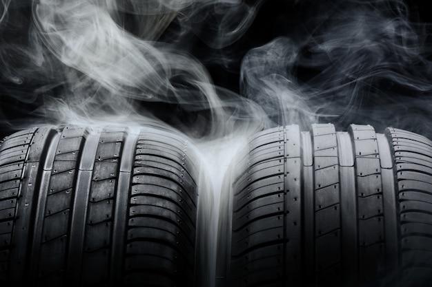 Pneumatici per auto e fumo sul nero
