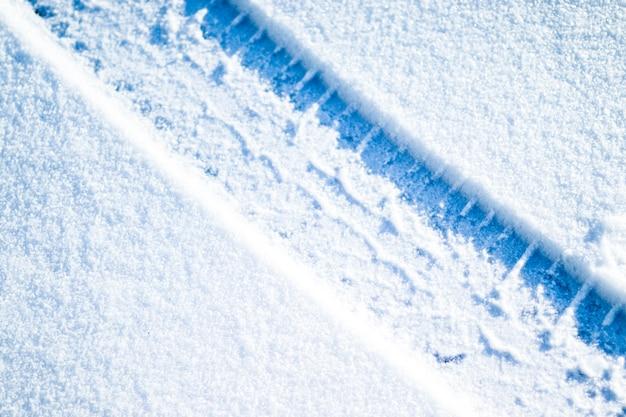 Pneumatici per auto sulla strada invernale. priorità bassa di inverno di natale con neve