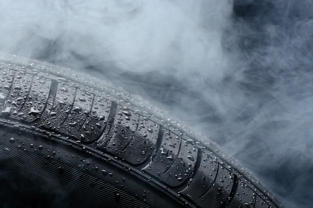 Pneumatico per auto coperto con gocce d'acqua nella nebbia