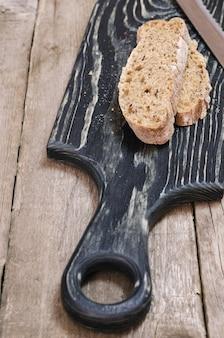 Pochi pezzi di pane sul tagliere di legno