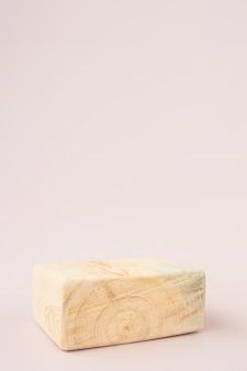 Podio quadrato strutturato in legno su sfondo chiaro.