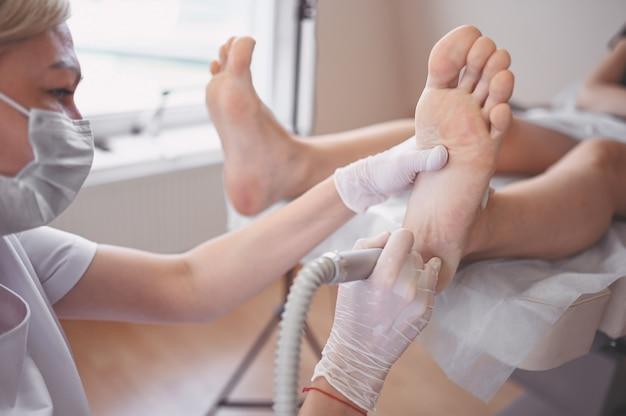 Podologo che utilizza attrezzature per la macinazione e lucidatura per pedicure dei piedi