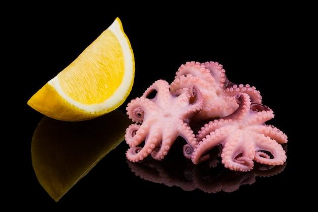 Polipo marinato del bambino con il limone sul nero