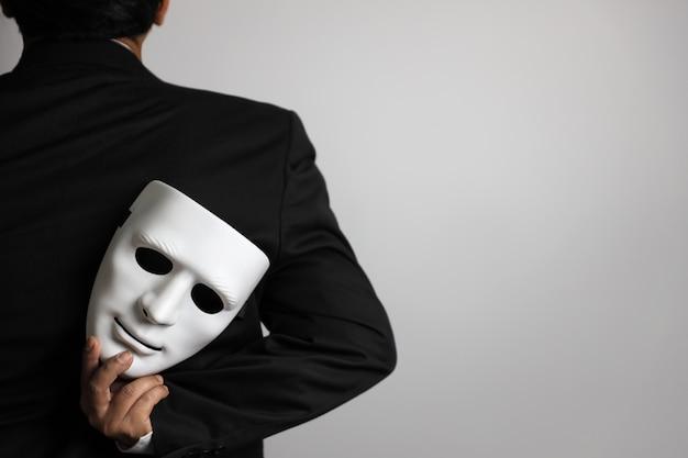 Politico o uomo d'affari che indossa vestito nero e maschera bianca nascondentesi
