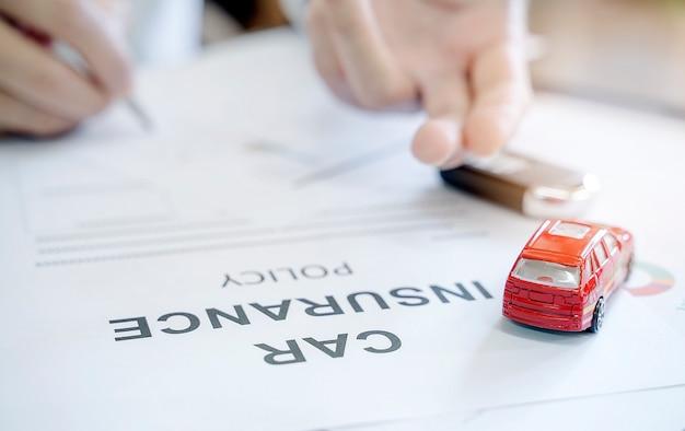 Polizza di assicurazione auto con giocattolo auto rossa e sfocatura immagine della mano dell'uomo