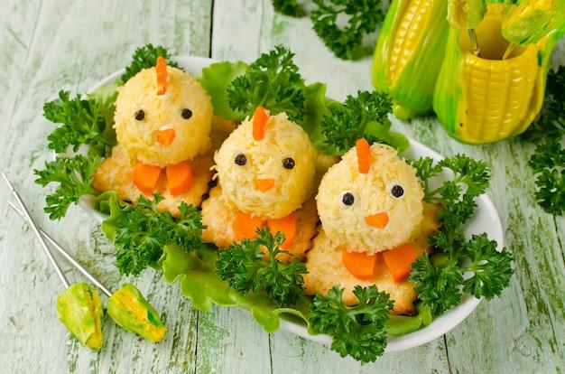 Polli divertenti dalle uova sulla tavola di pasqua
