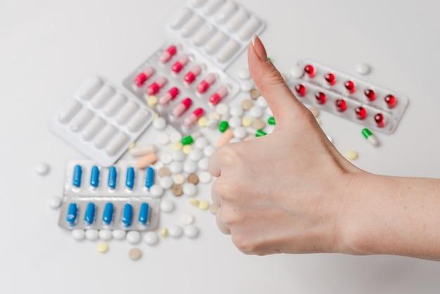 Pollice di mostra femminile in su per le pillole della medicina