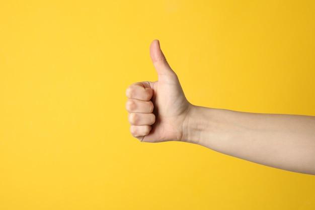 Pollice femminile su sfondo giallo, spazio per il testo