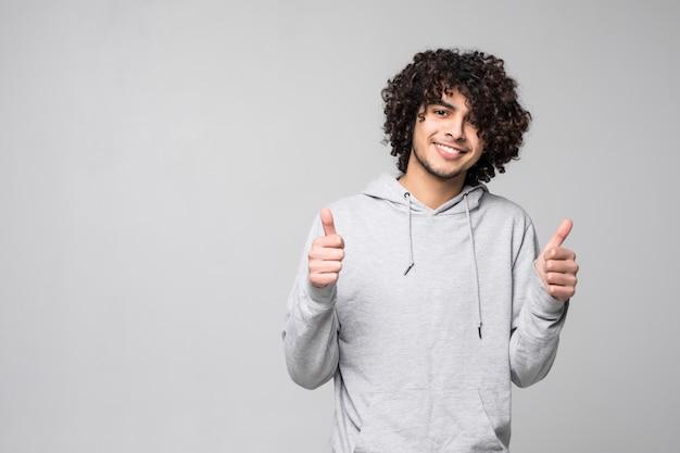 Pollice lshowing sorridente dell'uomo riccio su isolato su una parete bianca