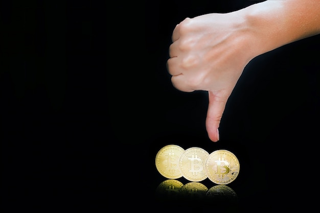 Pollice verso il basso segno della mano. bitcoin. bitcoin e nuovo concetto di denaro virtuale. bitcoin è una nuova valuta.