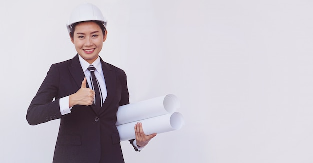 Pollici asiatici di manifestazione della ragazza dell'ingegnere su su fondo bianco