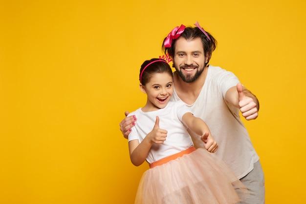 Pollici gialli del padre e della figlia in su