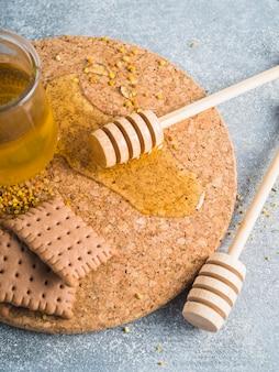 Polline d'api; miele; biscotti e mestolo di legno su sottobicchiere di sughero