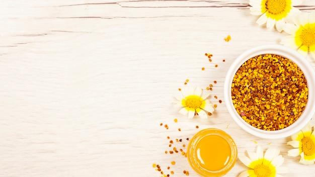 Polline dell'ape e del miele con il bello fiore sullo scrittorio di legno bianco
