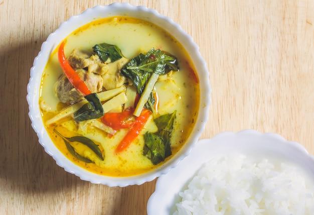 Pollo al curry con germogli di bambù e riso cotto in una ciotola bianca sul tavolo di legno.