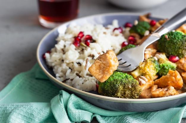 Pollo al curry con riso, funghi e broccoli decorati con semi di melograno